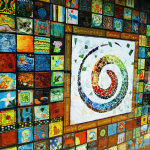 A mosaic wall made up of individual ceramic tiles arranged in a quilt-like pattern. Each tile was individually painted by a member of the community and all are unique. In the center of the mosaic there is a large rainbow swirl done in recycled beach glass. This swirl is the Garden's logo.