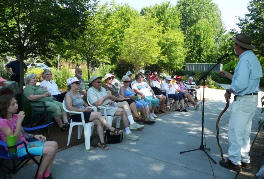 man stands in front of an audience in an outdoor garden